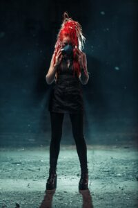 Punk woman with bright red hair wearing black clothes and black surgical mask