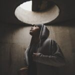 Man in hoodie with eyes closed standing under a hole in a concrete ceiling
