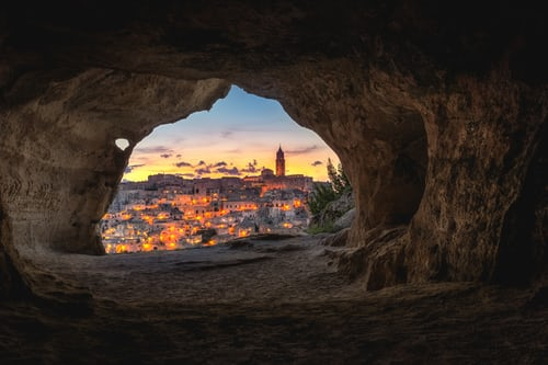 View of a city full of lights seen through the mouth of a cavern