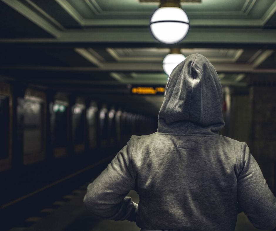 Gray hoodie worn by someone waiting for a train