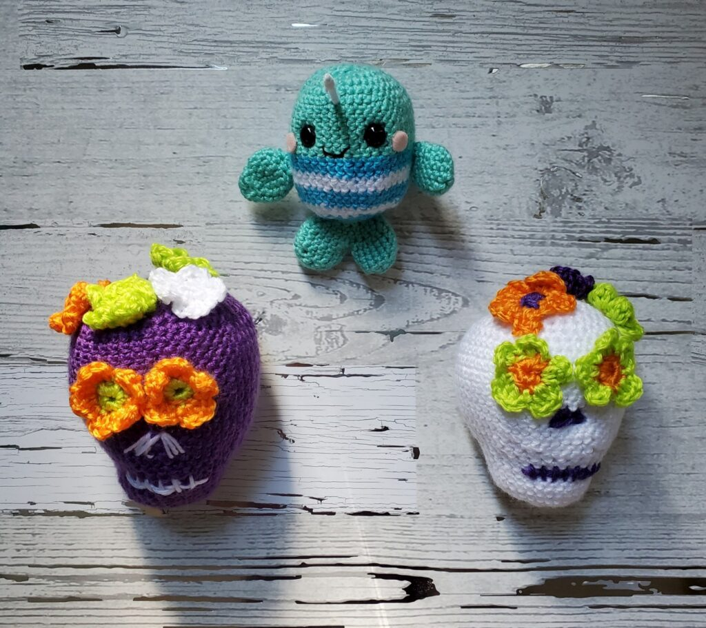 Three amigurumi collectibles: aqua narwhal, purple sugar skull, and white sugar skull.