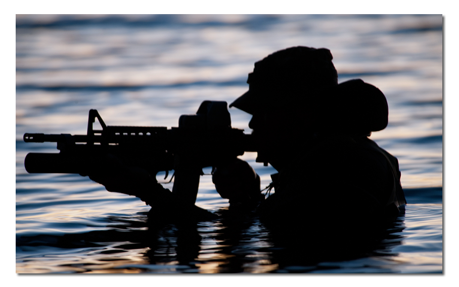 Image: Silhouette of U.S. Navy Seal arising from water revealing only the outline of his head, shoulders, and rifle.