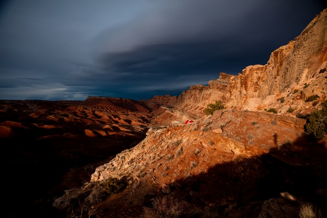 Dark storm clouds hang over rocky  desert ridges.