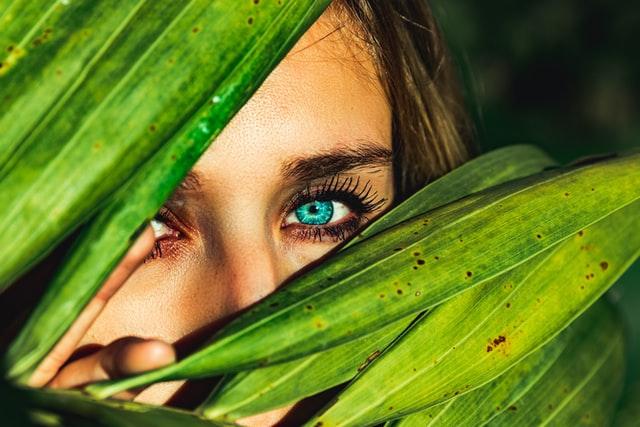 Woman with blue eyes peering between green leaves