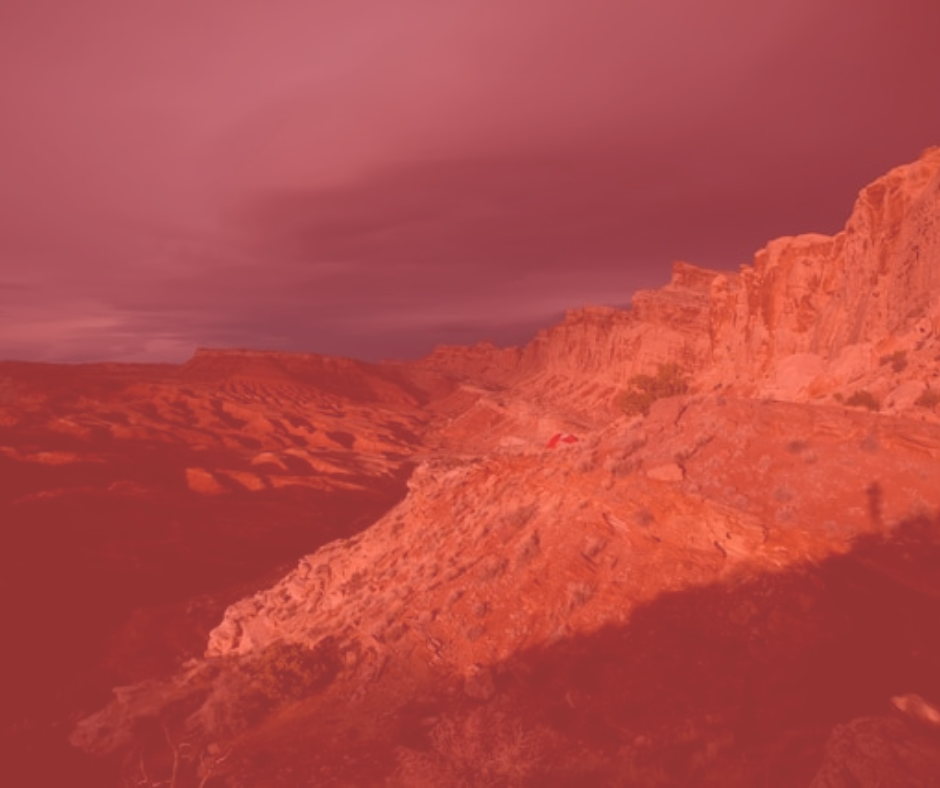 Rocky desert ground with rocky cliffs to the right and an ominous stormy sky overhead, all with an ominous red coloration.