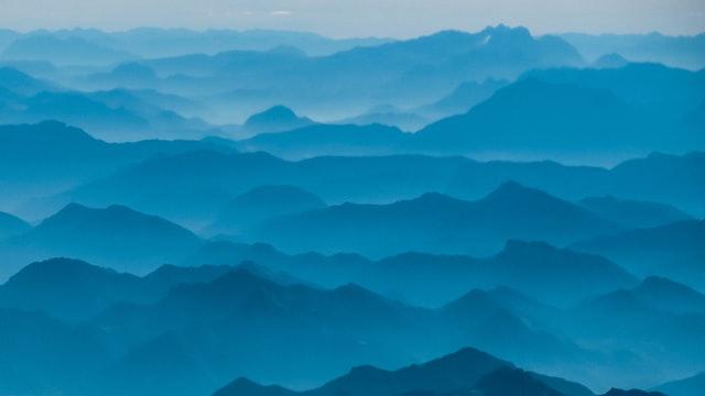 Mist rising between blue mountain ridges