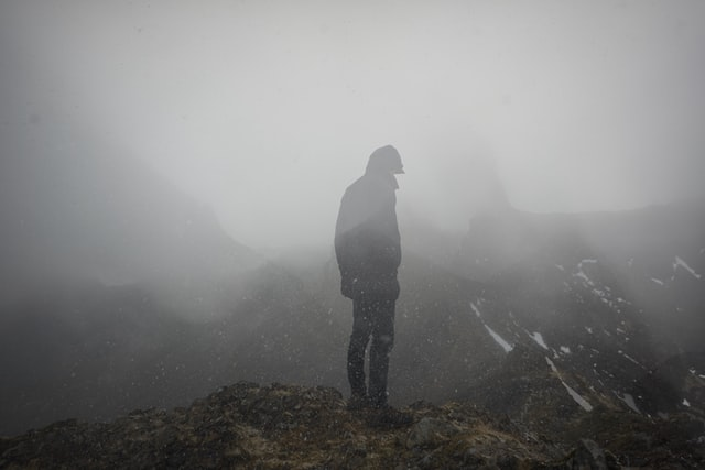 Man standing on mountaintop, superimposed with images of snowy mountaintops.