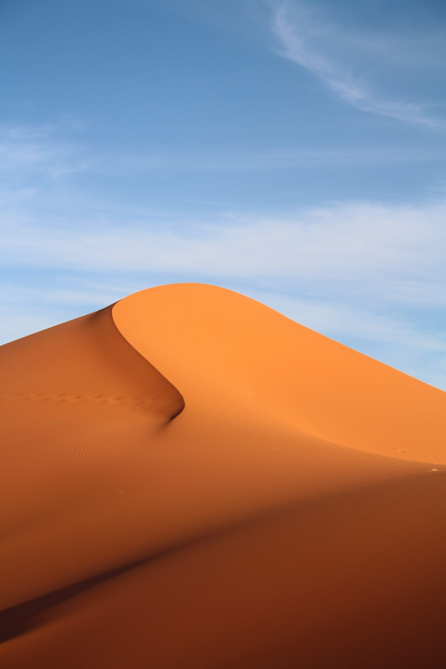 A tall, tan sand dune with a sinuous front curve reaches high into a blue sky.
