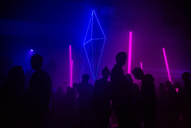 Silhouettes of people standing in a dark room lit partially by beams of purple light.